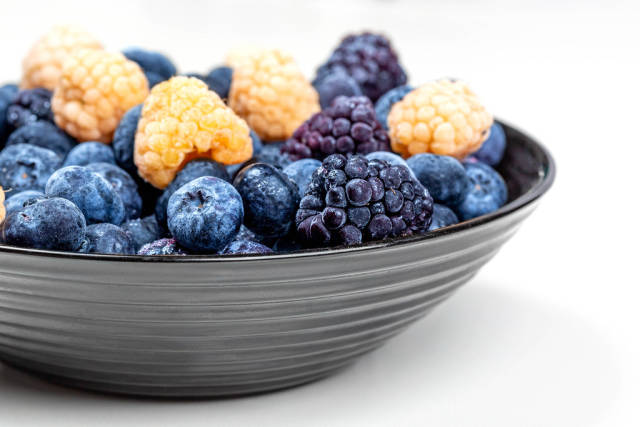 Bowl with blueberries, yellow raspberries and mulberries