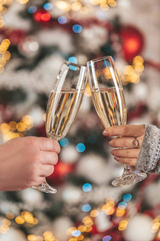 Close up, photo of two people holding glasses of champagne on xmas bokeh background
