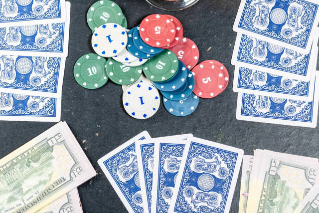 Blue cards with chips and dollars on the table. The concept of gambling