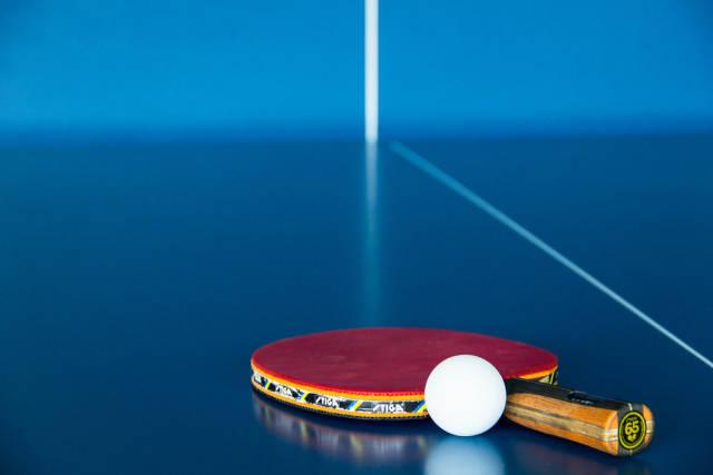 Tischtennisschläger und Ball auf der Platte