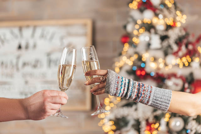 Christmas celebration background with two glasses of champagne in the hands of a man and a woman