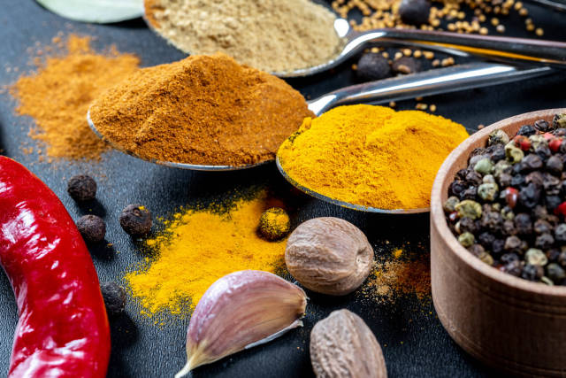 Multi-colored spices for healthy and tasty cooking on a black background