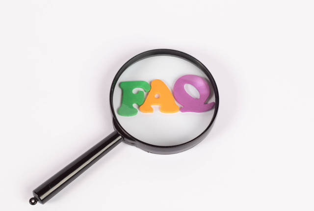 Magnifying glass on letters as FAQ abbreviation