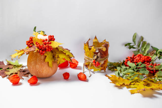Autumn background with glowing candles, pumpkin and yellow leaves
