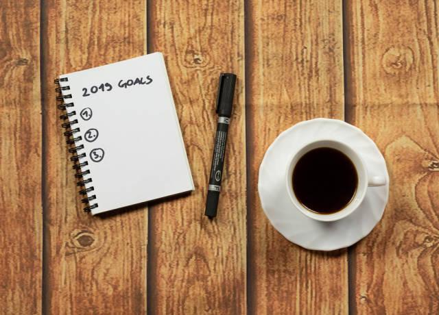 Ziele im neuen Jahr 2019 geschrieben in einem Notizbuch das auf einem Holztisch liegt