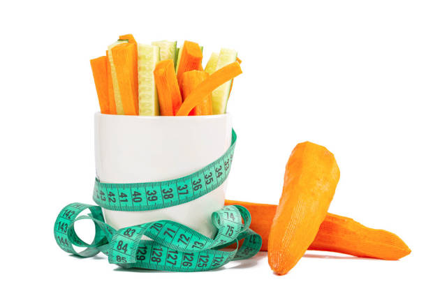 Sliced fresh carrots and cucumbers with a measuring tape on a white background
