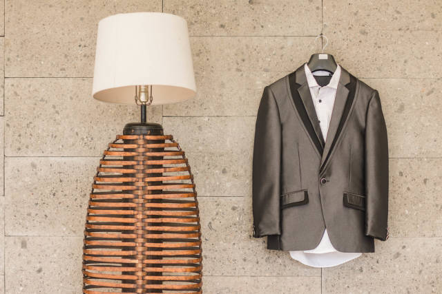Grooms Suit hanging next to a lamp