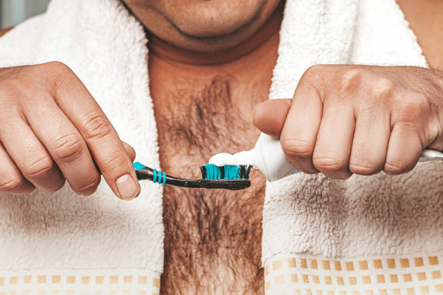 A man with a towel squeezes toothpaste on a toothbrush. The concept of dental care