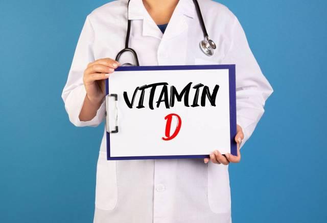 Arzt hält einen Schild mit der Schrift Vitamin D im blauen Hintergrund