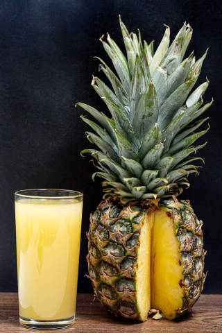 Glass of fresh pineapple juice with ripe pineapple