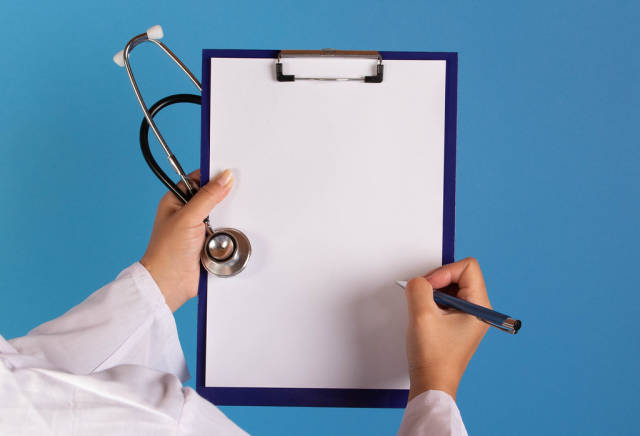 Doctor writting on clipboard