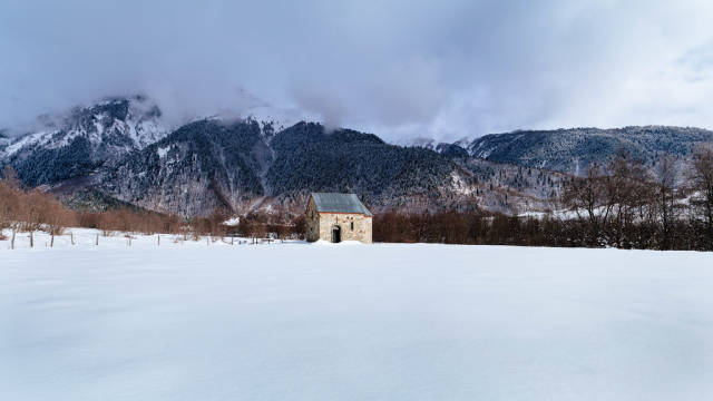 Small stone church in the middle of nowhere surrounded by snow and mountains
