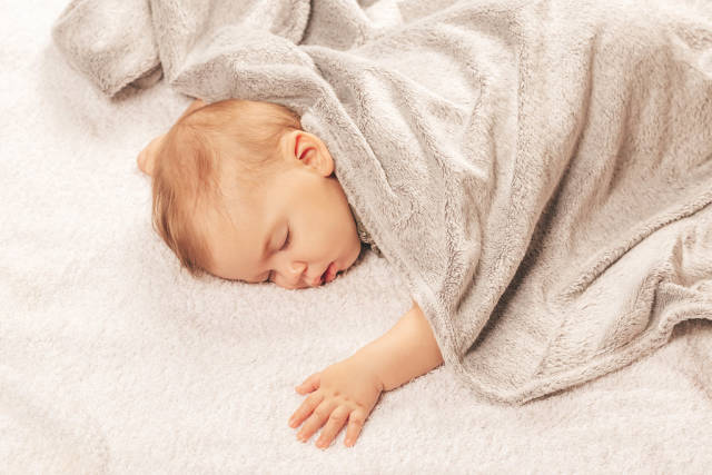 Sweetly sleeping baby covered with a gray blanket