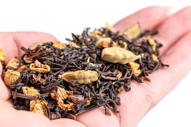 Spiced dry black tea with spices on hand, close-up
