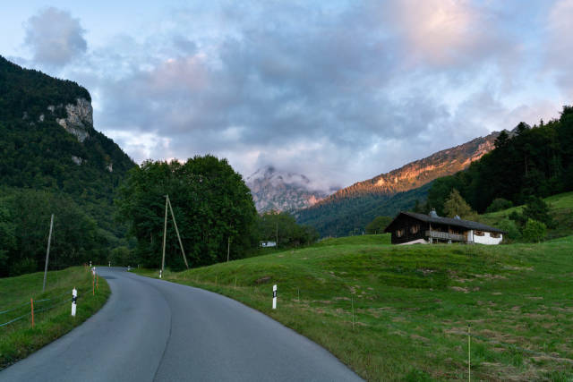 Beautiful Swiss country road going up the mountains with sunset mountain peak at the end