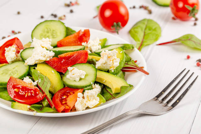 Fresh vegetable salad with tomatoes, cucumbers, avocado, cottage cheese and beet leaves