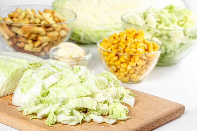 Sliced chinese cabbage with corn and croutons, salad preparation