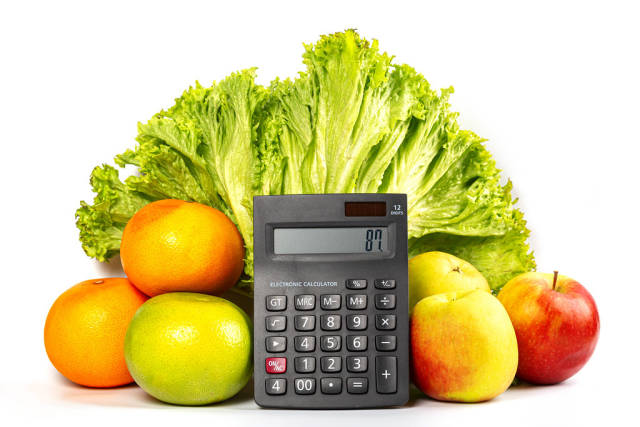 Lettuce, fruits and calculator on a white background, the concept of calories, weight loss and healthy diet