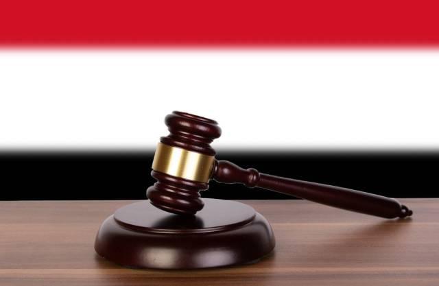 Wooden gavel and flag of Yemen