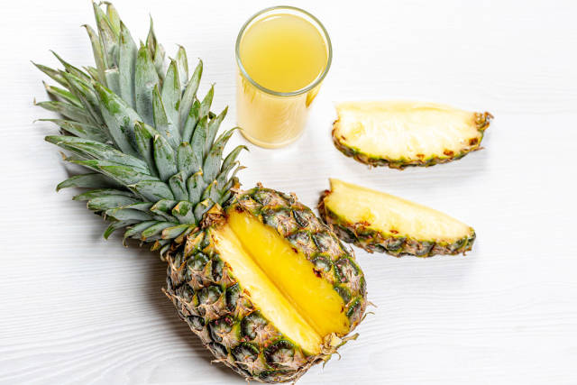 Ripe pineapple and a glass of pineapple juice