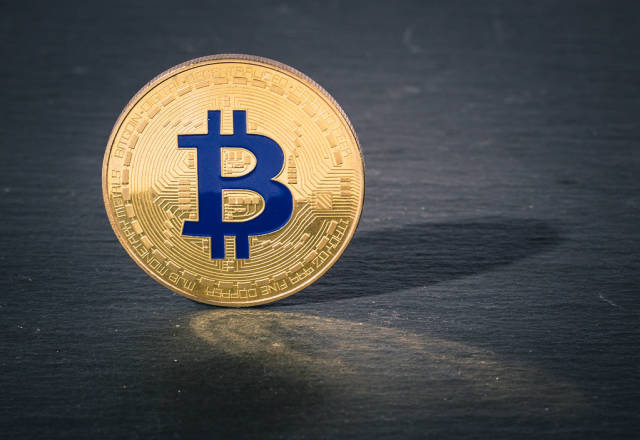 Close up photo of a golden Bitcoin on a black background