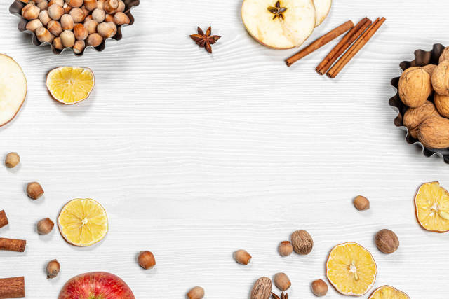 Frame with nuts spices dried citrus and fresh slices apple on a white wooden background. The view from the top