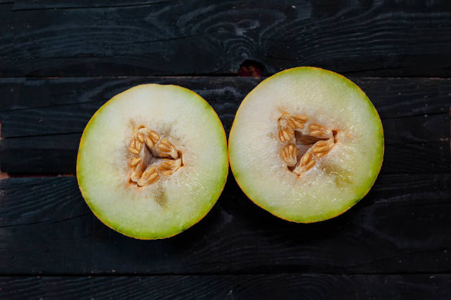 Two slice of sweet melon on the dark wooden background