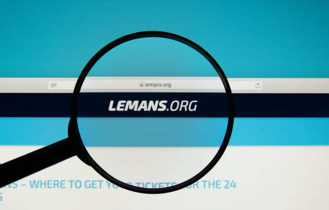 24 Hours of Le Mans official website on a computer screen with a magnifying glass