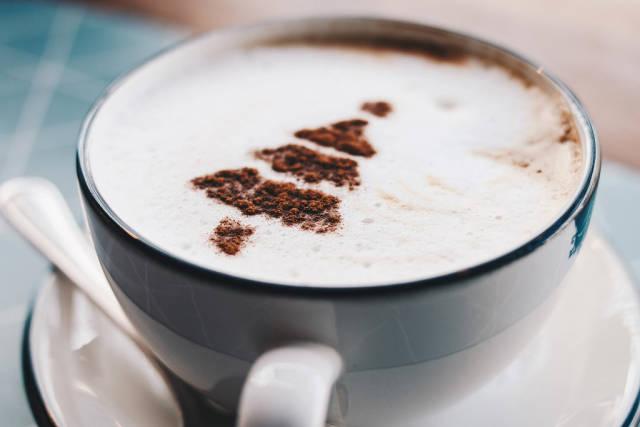 Nahaufnahme von einer Tasse Cappuccino mit Kakao in Weihnachtsbaum-Gestalt
