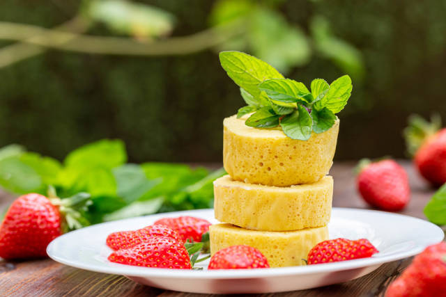 Pieces of sweet roll with fresh strawberries and mint on a blurred background of nature