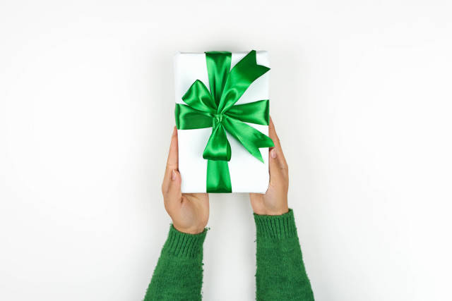 Woman giving a beautiful present with a green textile ribbon