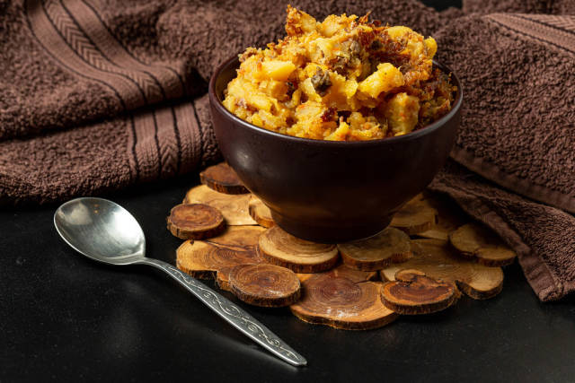 Stewed potatoes with vegetables and meat on a dark background