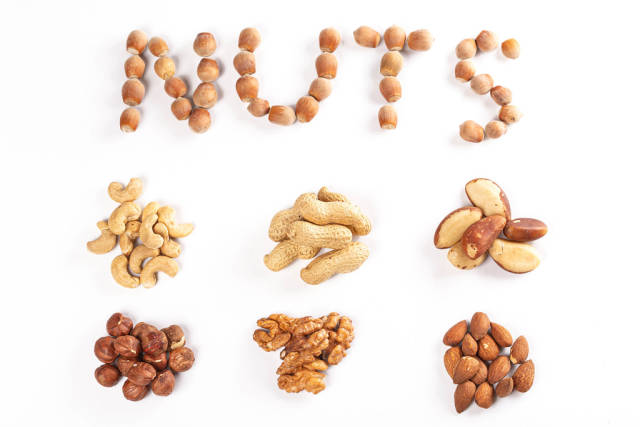 Top view, set of different types of nuts on a white background