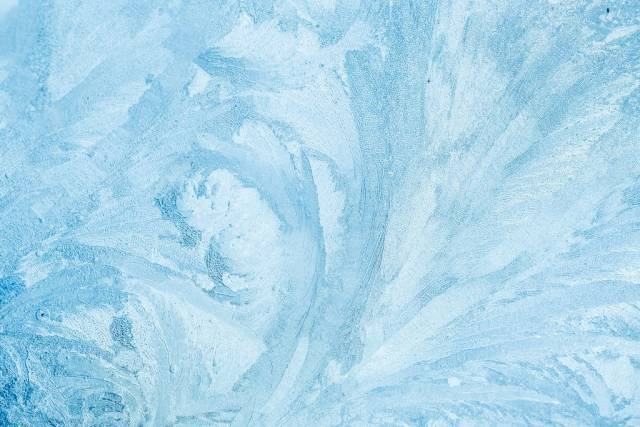 Frozen glass with beautiful ice patterns in light blue