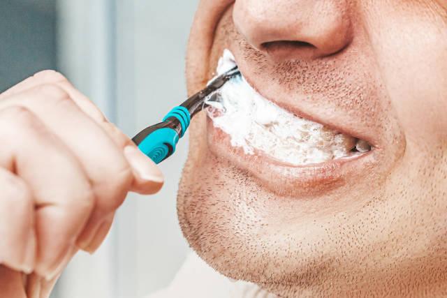 Man brushing his teeth in bathroom