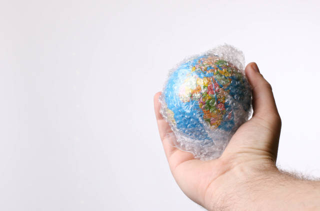 Hand holding globe packed in bubble wrap