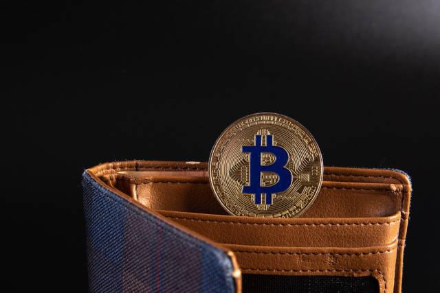 Open wallet with golden Bitcoin coin