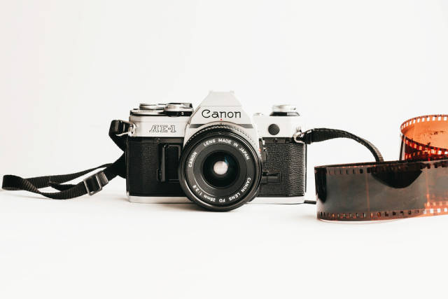 Canon AE-1 film camera and roll of developed film on white background