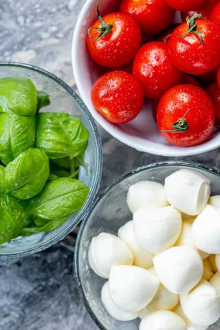 Top view ripe tomatoes, fresh garden basil and mozzarella cheese