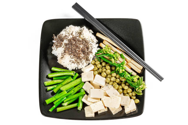 Rice, peas, broccolini, cheese and chia seeds on a black plate, top view