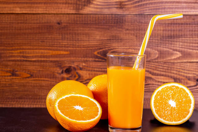 Fresh squeezed natural orange juice with oranges on wooden background
