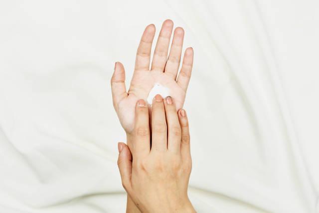 Young woman applying hand cream