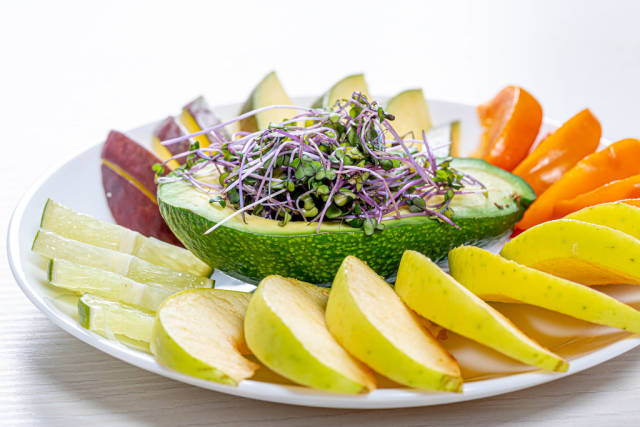 Fresh fruit slicing on a white plate with avocado and micro green cabbage