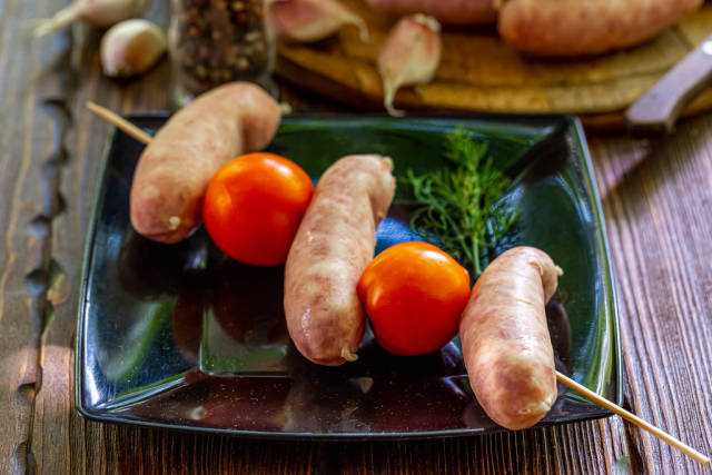 Wooden skewer with raw sausages and tomatoes on a black plate