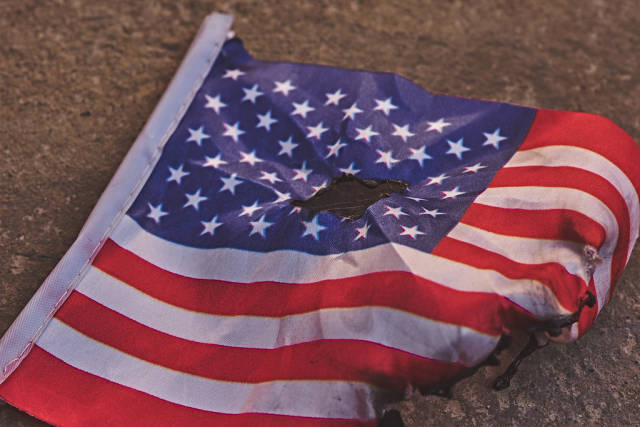 Dirty and torn american flag on the ground