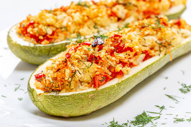 Closeup of baked zucchini halves with vegetables and couscous
