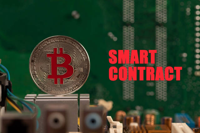 Silver Bitcoin on computer parts with Smart Contract text