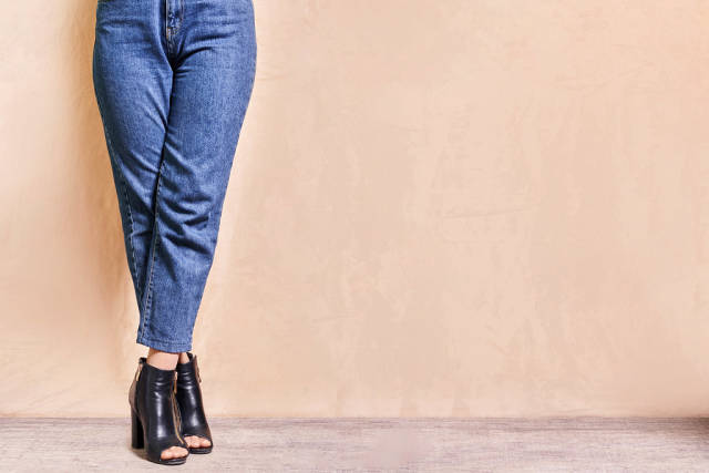 A stylish girl in jeans standing legs crossed over bright background