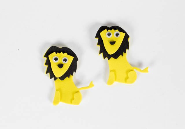 Zwei Spielzeug-Löwen vor weißem Hintergrund