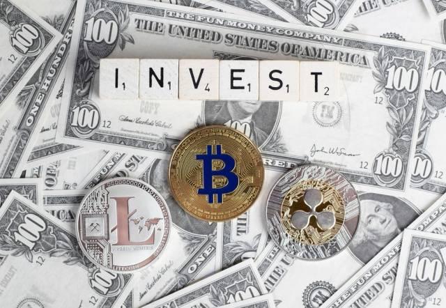 Das Wort INVEST und Kryptowährungsmünzen = In Kryptowährungen investieren